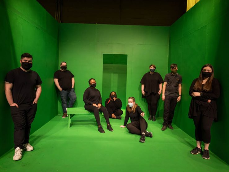 students wearing black in a green screen room