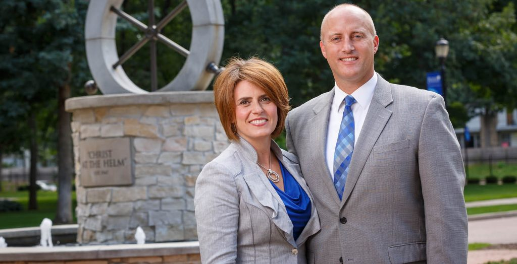 Bethel University President Gregg Chenoweth and wife Tammy stand in front of the helm