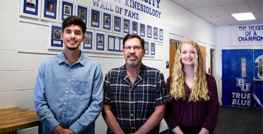 Kole Hanke, Larry McClements and Grace Haley stand in front of the Kinesiology Wall of Fame at Bethel University