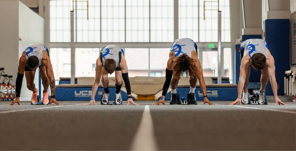four male track athletes at the starting line in the Lehman Family Training Center
